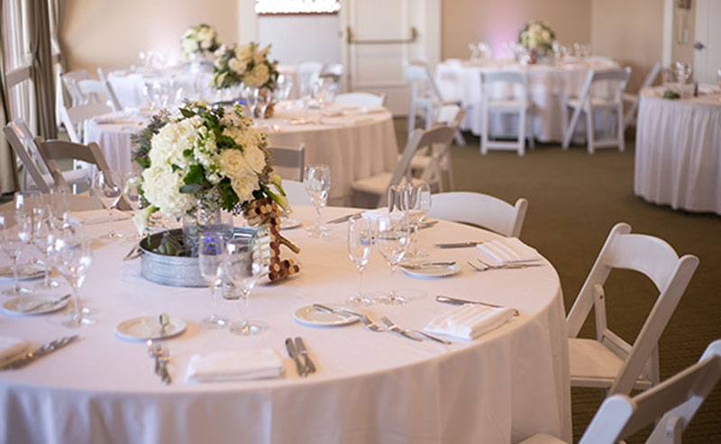 Tables, chairs, dinnerware and decorations set up for a wedding reception in the Acapulco Room at La Jolla Shores Hotel
