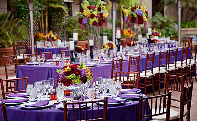 Tables, chairs, dinnerware and decorations set up for a wedding reception on the La Jolla Patio at La Jolla Shores Hotel