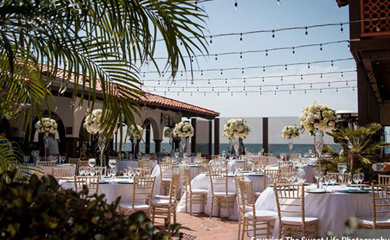 Tables, chairs, dinnerware and decorations set up for a wedding reception on the Shores Patio at La Jolla Shores Hotel