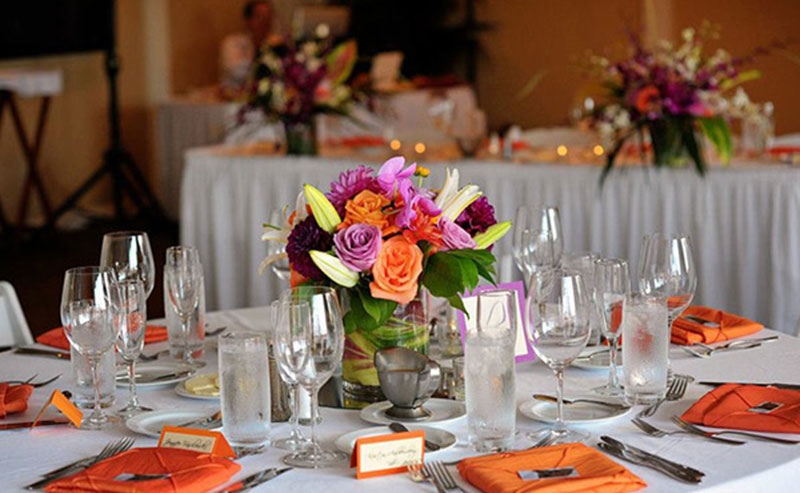Tables, chairs, dinnerware and flowers set up for a wedding reception in the Acapulco Room at La Jolla Shores Hotel