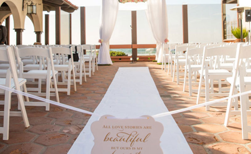 Wedding ceremony set up with chairs, and a wedding arch on the Shores Patio at La Jolla Shores Hotel