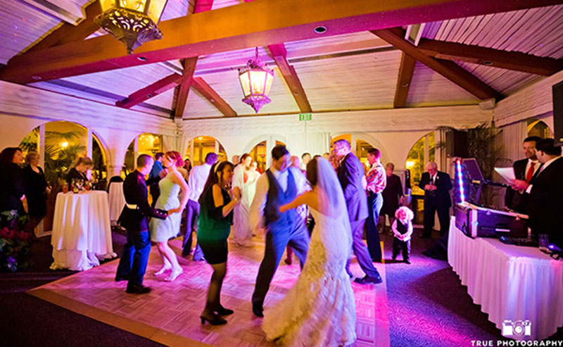 Wedding guests dancing on the dancing floor in the La Jolla Room at La Jolla Shores Hotel