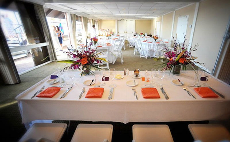Wedding party table set up with chairs, flowers and dinnerware in the Acapulco Room at La Jolla Shores Hotel