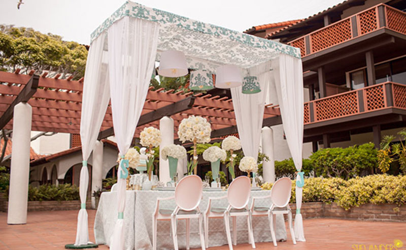 Wedding party table set up with chairs, flowers, dinnerware under a sheeted awning in the Garden Patio at La Jolla Shores Hotel