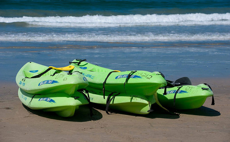 Green kayaks stacked on top of eachother at La Jolla Shores beach along the coastline