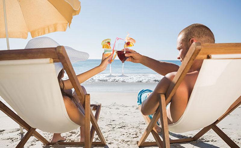 A couple lounging in chairs at La Jolla Shores beach, toasting to eachother