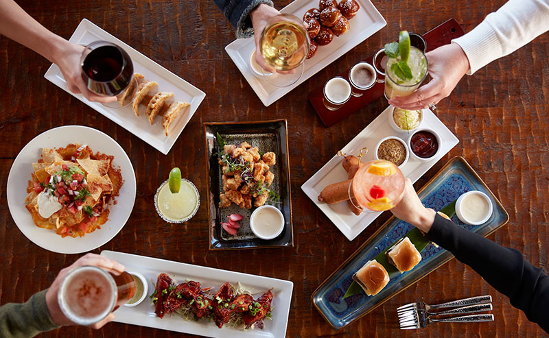 An overhead shot of a table filled with appetizers and drinks at La Jolla Shores Hotel happy hour