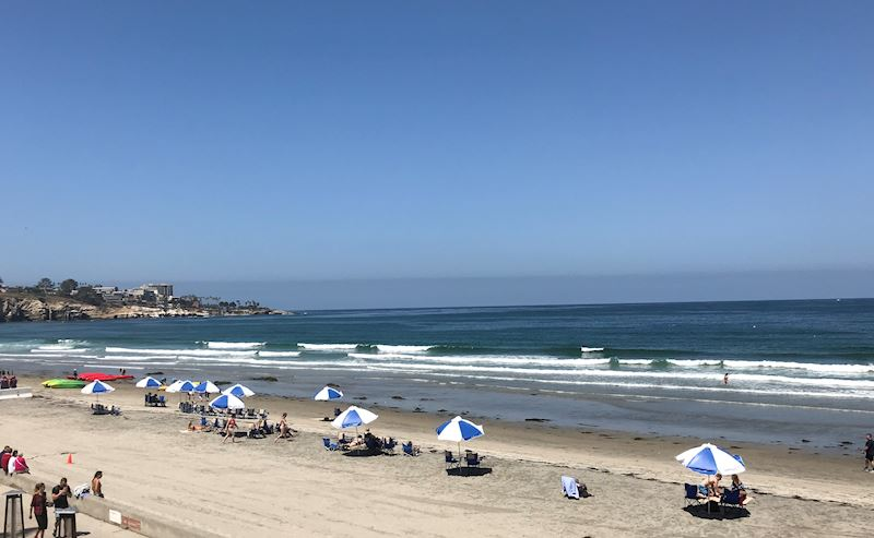 A view of La Jolla Shores beach looking toward La Jolla Cove, showing the hotel's umbrella and chair set ups which are complimentary for guest use.