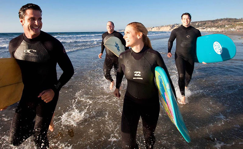 Four La Jolla Shores Hotel guests heading out to the ocean to go surfing