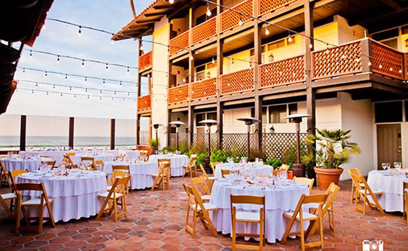 Tables and chairs set up for a meeting at the La Jolla Shores Hotel Patio overlooking the beach