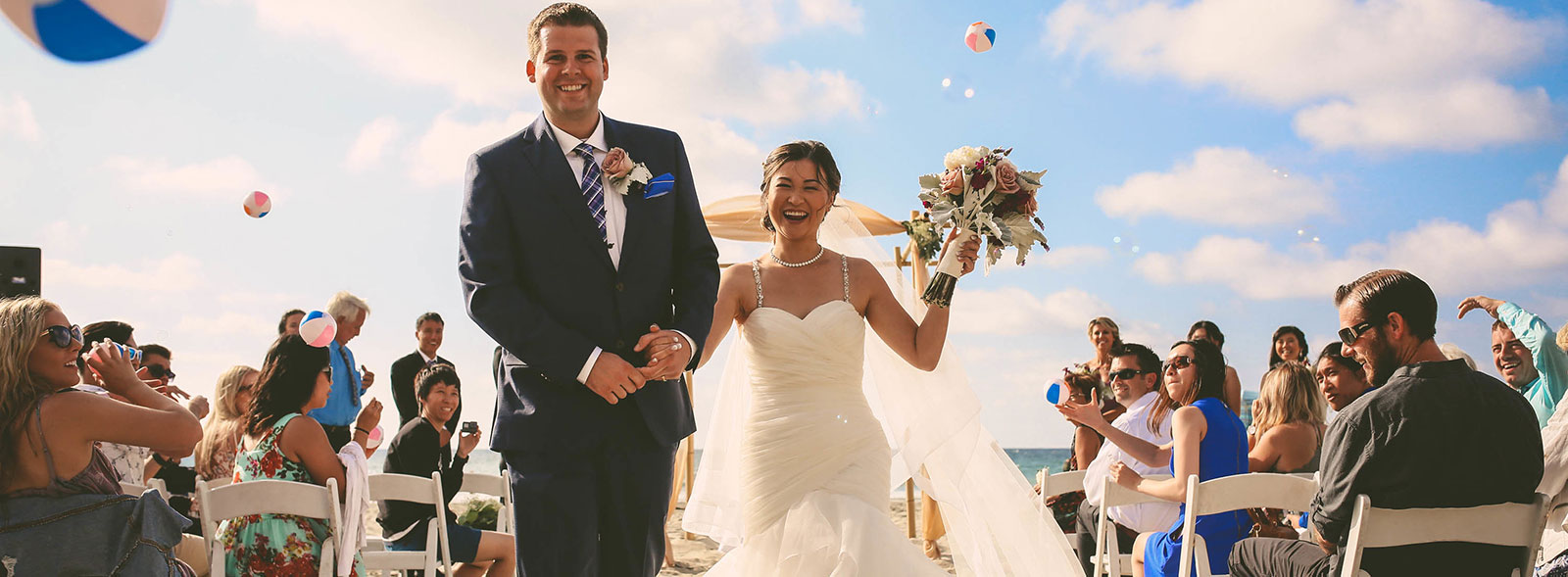 A couple walking down the aisle after their beach wedding ceremony at La Jolla Shores Hotel