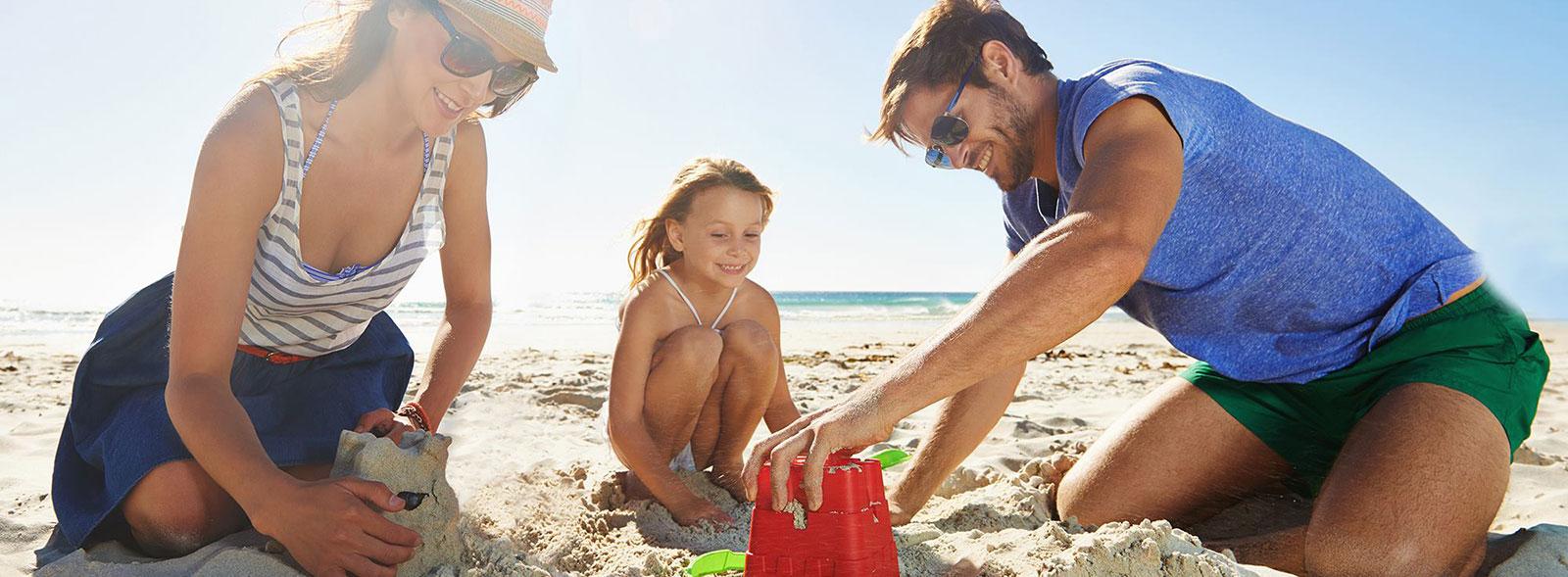 A family of three building sand castles at La Jolla Shores beach