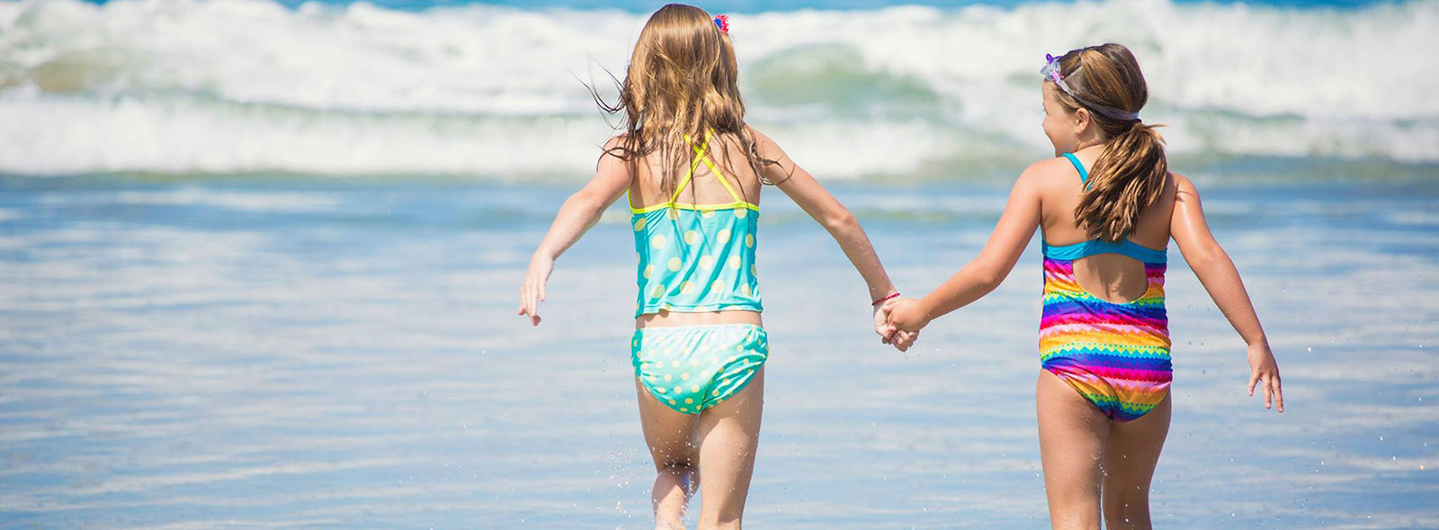 Two little girls holding hands, running into the ocean at La Jolla Shores beach